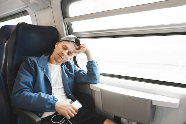Sleepy student sleeps in the train in the morning and listens to music the headphones.
