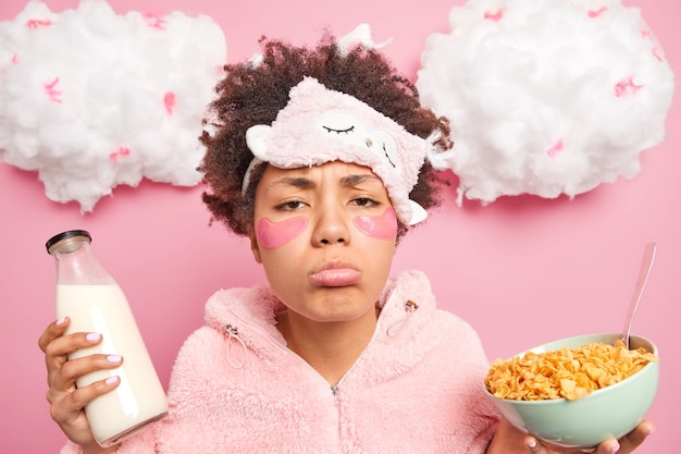 La donna afroamericana imbronciata sonnolenta con espressione triste indossa indumenti da notte mangia cibo sano applica patch di collagene sotto gli occhi pone contro il muro rosa