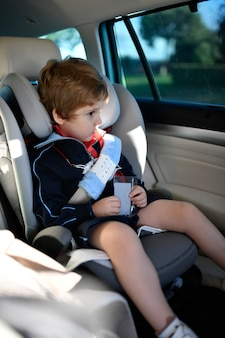 Sleepy three year old boy sitting in car safety seat going to school in the morning