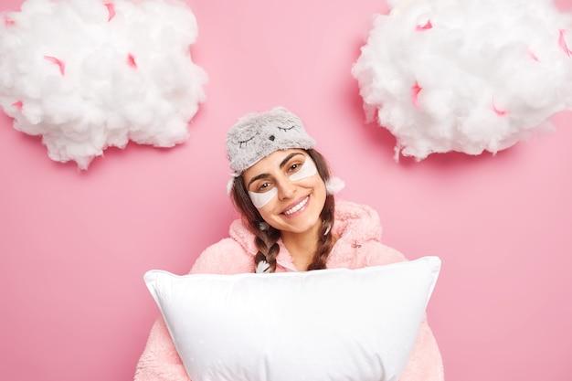 Время сна. позитивная симпатичная девушка наклоняет голову, улыбается, нежно носит ночное белье