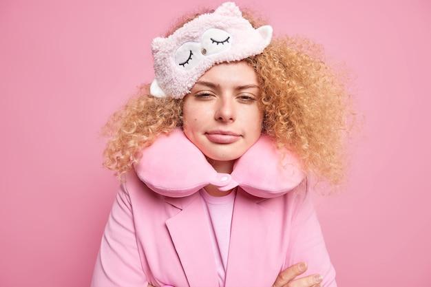 眠そうな疲れた縮れ毛の女性は、ピンクの壁に隔離されたハードワークの日の後、頭に目隠しをして首の周りの快適な枕を早く目覚めさせます。睡眠の概念。