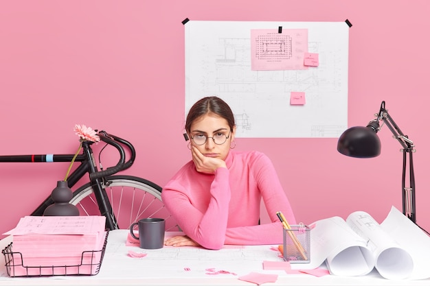 Sleepy tired female office worker checks outaly of architectural project worked all day long on creating sketches wears turtleneck and spectacles draws blueprint of construction poses at desktop