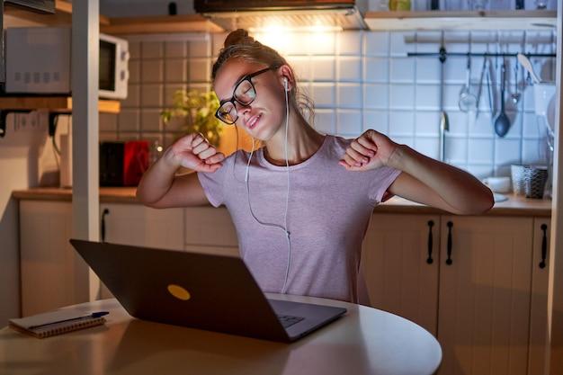 졸린 피곤 과로 워커 홀릭 여자 안경과 근육을 스트레칭 헤드폰을 착용하고 늦은 저녁에 노트북에서 열심히 일하는 동안 휴식을 취