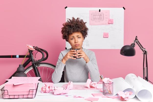 Сонная уставшая женщина пьет кофе за столом с бумажными обрывками, весь день работает над строительным проектом, готовит архитектурные эскизы, сидит в коворкинге, обладает творческими способностями
