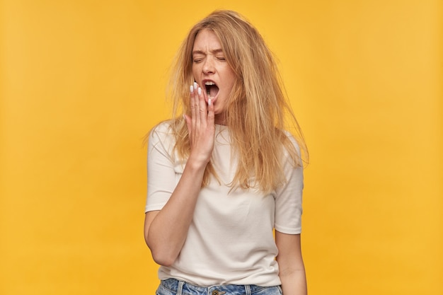 Sleepy tired woman with freckles messy hair and closed eyes in white tshirt looks exhausted and yawning on yellow