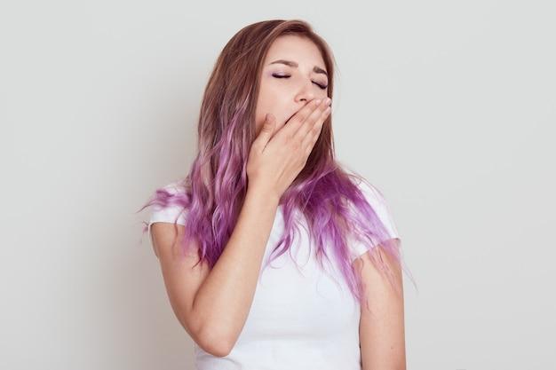 眠そうな疲れた若い女性は、あくびをしている白いカジュアルなtシャツを着て、開いた口を手のひらで覆い、口を閉じたままにし、もっと眠る必要があり、灰色の壁の上に孤立してポーズをとります。