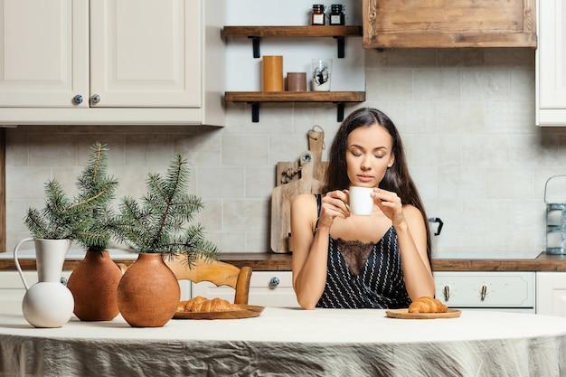 台所で淹れたてのコーヒーを飲む眠そうな女性
