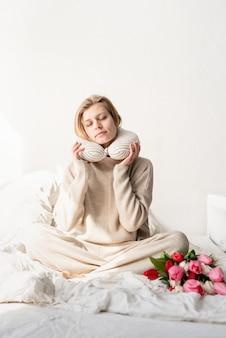 首にパジャマと枕、ベッドにチューリップの花を着てベッドに座っている眠そうな女性