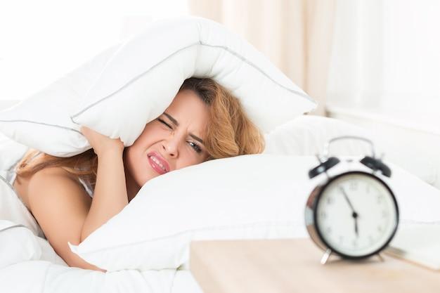 朝枕の下に隠れようとしている眠そうな女性
