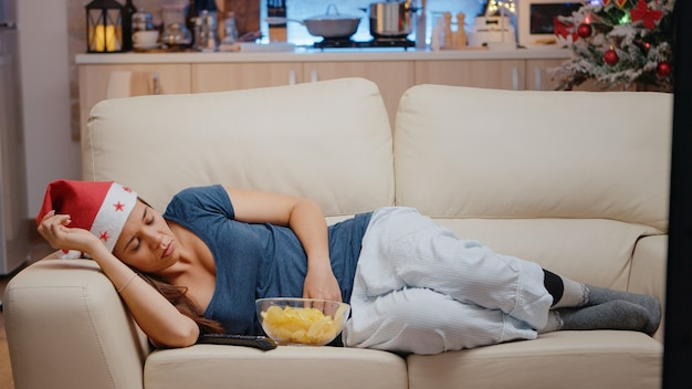 ソファでテレビを見ているサンタ帽子を持つ眠そうな女性