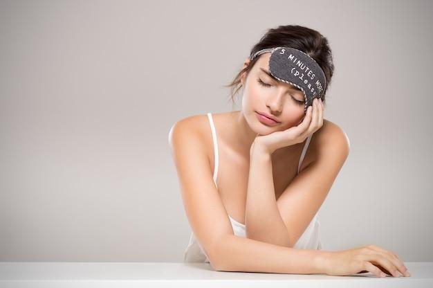 眠っているマスクを持つ眠そうな女性