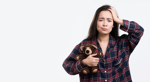 Sleepy woman with teddy bear