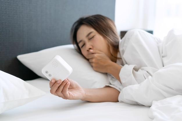 眠そうな若いアジア人女性がベッドで寝て、目覚まし時計を消したり、朝の時間をチェックしたりする
