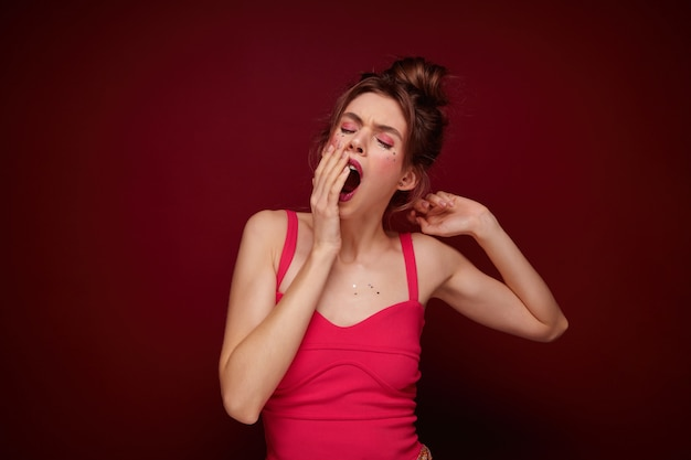 Sleepy young attractive brown haired female in festive clothes covering her mouth with raised palm and yawning with closed eyes, coming home after party with friends, isolated