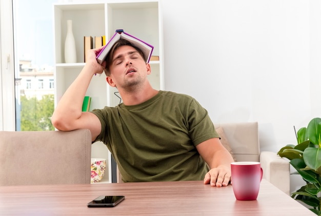 Assonnato giovane biondo bell'uomo si siede al tavolo con tazza e telefono che tiene il libro sopra la testa con gli occhi chiusi all'interno del soggiorno