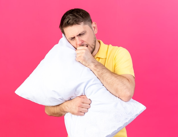 Sleepy young blonde ill man yawns and holds pillow isolated on pink wall