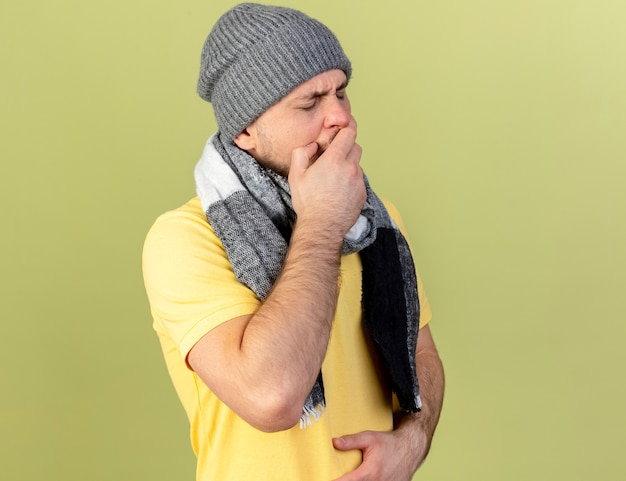 Sleepy young blonde ill slavic man wearing winter hat and scarf yawns putting hand on mouth isolated on olive green wall with copy space