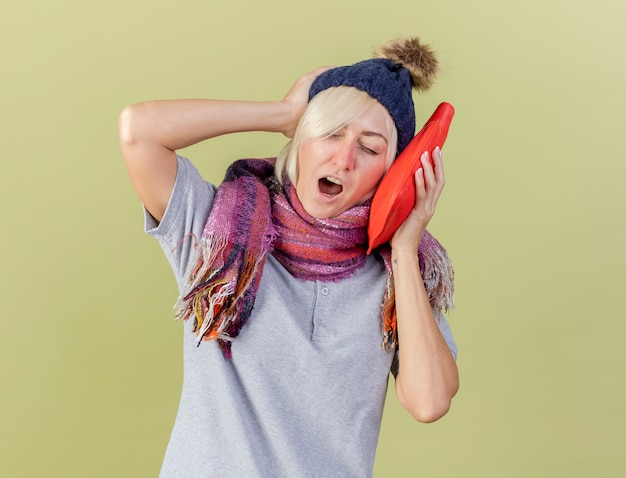 겨울 모자와 스카프 하품을 입고 졸린 젊은 금발의 아픈 슬라브 여자가 머리에 손을 넣고 복사 공간이 올리브 녹색 벽에 고립 된 뜨거운 물병을 보유하고 있습니다.