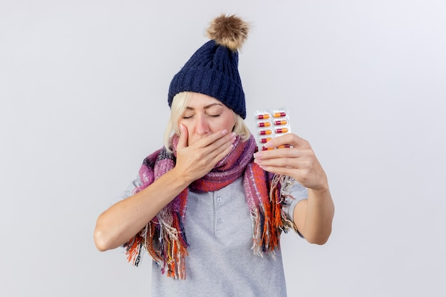 Sleepy young blonde ill slavic woman wearing winter hat and scarf yawns putting hand on mouth and holds pack of medical pills isolated on white wall with copy space