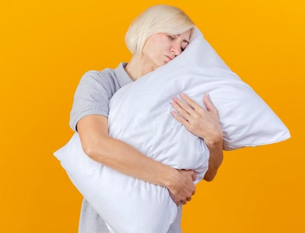 La giovane donna ammalata bionda assonnata abbraccia e mette la testa sul cuscino isolato sulla parete arancione
