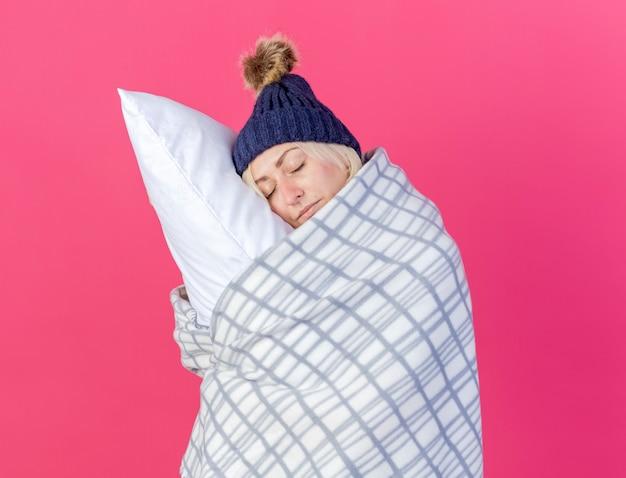 Giovane donna bionda malata sonnolenta che indossa cappello invernale e sciarpa avvolta in abbracci plaid e mette la testa sul cuscino isolato sul muro rosa