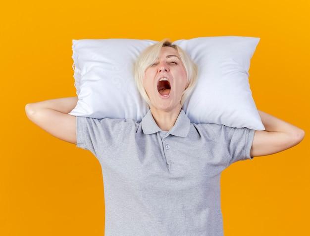 眠そうな若い金髪の病気の女性はあくびをして、オレンジ色の壁に隔離された頭の後ろに枕を保持します