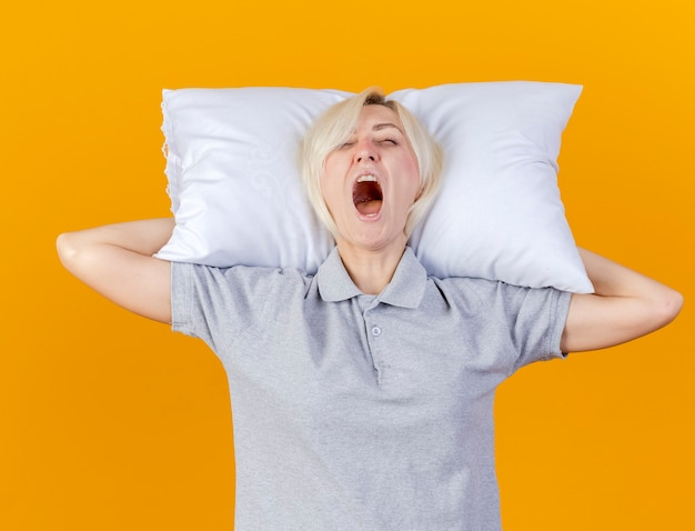 Sleepy young blonde ill woman yawns and holds pillow behind head isolated on orange wall