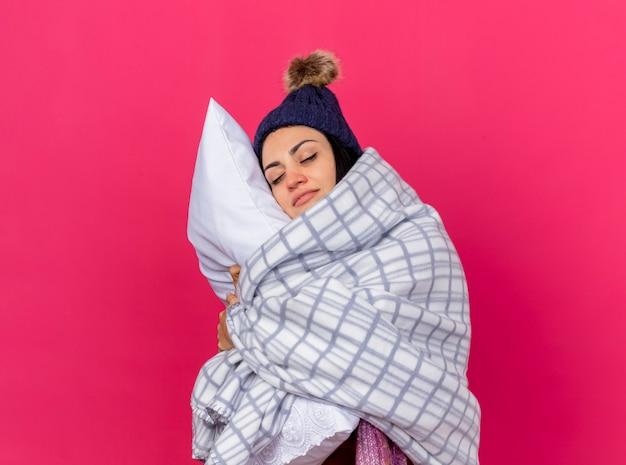 Assonnata giovane ragazza caucasica malata che indossa cappello invernale e sciarpa avvolti in plaid che abbraccia cuscino mettendo la testa su di esso con gli occhi chiusi isolati sulla parete cremisi con spazio di copia