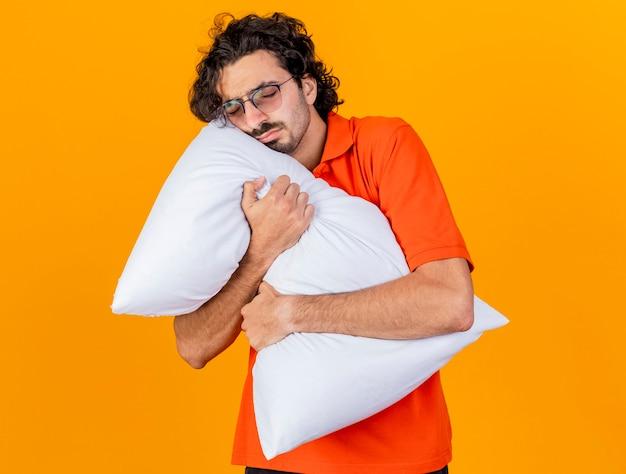 Assonnato giovane indoeuropeo uomo malato con gli occhiali abbracciando cuscino con gli occhi chiusi isolato su sfondo arancione con copia spazio