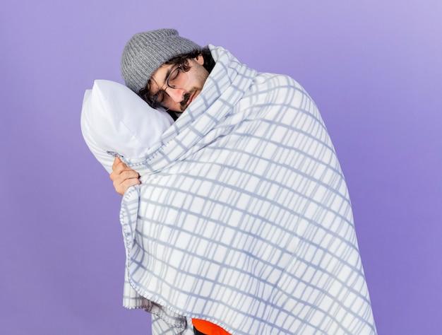 眠そうな若い白人の病気の人は、紫色の背景に分離された目を閉じて頭を置く枕を保持している格子縞に包まれた眼鏡の冬の帽子とスカーフを身に着けています