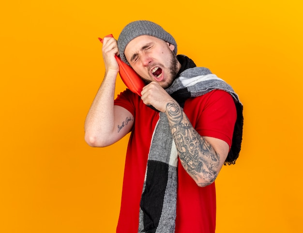 Sleepy young caucasian ill man wearing winter hat and scarf yawns and puts head on hot water bottle isolated on orange wall with copy space