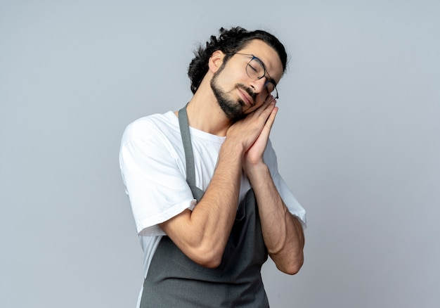 Sleepy young caucasian male barber wearing glasses and wavy hair band in uniform doing sleep gesture with closed eyes isolated on white background with copy space