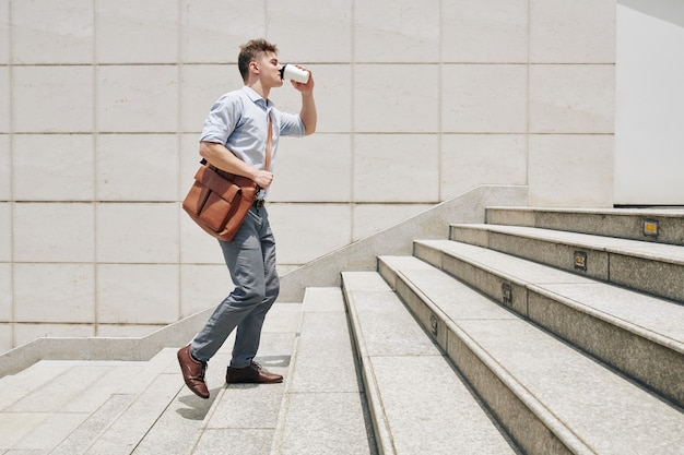 서둘러 출근하고 커피를 마시면 계단을 올라가는 졸린 젊은 기업가