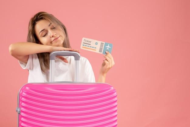 チケットを保持しているピンクのスーツケースを持つ眠そうな少女