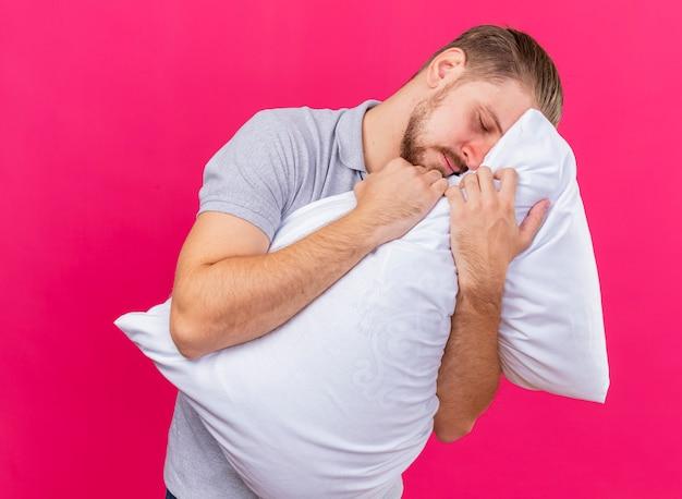 Сонный молодой красивый славянский больной обнимает подушку, кладя на нее голову с закрытыми глазами, изолированными на малиновом фоне