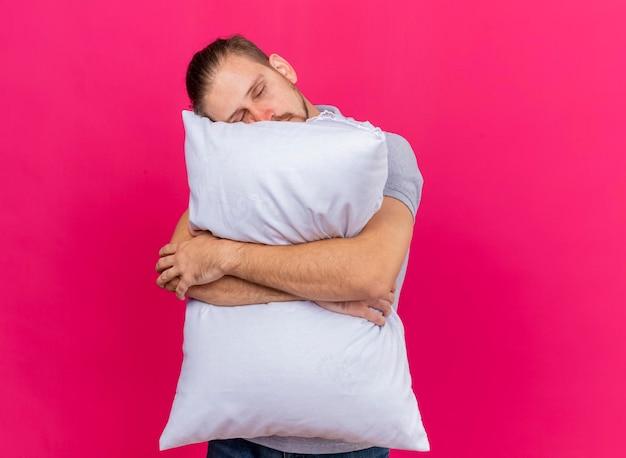 眠そうな若いハンサムなスラブの病気の人が枕を抱き締めて、コピースペースのあるピンクの壁に隔離された目を閉じて頭を置く