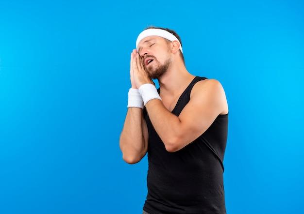Сонный молодой красивый спортивный мужчина в головной повязке и браслетах, делающий жест сна, изолированный на синем пространстве