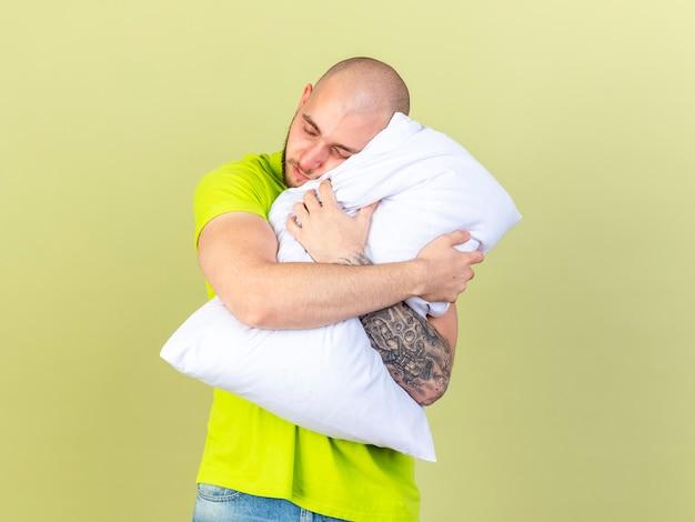 졸린 젊은 아픈 남자가 포옹하고 올리브 녹색 벽에 고립 된 베개에 머리를 넣습니다.