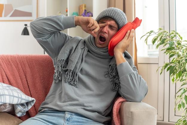 목에 스카프를 두른 졸린 젊은이가 겨울 모자를 쓰고 손가락으로 눈을 닦고 거실 소파에 앉아 뜨거운 물병을 들고 있다