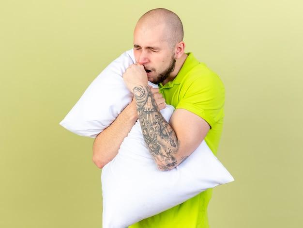 眠そうな若い病気の男はあくびをし、オリーブグリーンの壁に分離された枕を保持します