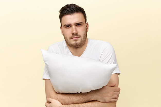 Sleepy young male posing with cushion. attractive guy with bristle having tired facial expression because of insomnia trying to fall asleep, holding pillow.