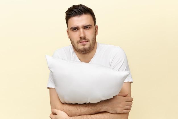 Сонный молодой мужчина позирует с подушкой. привлекательный парень с щетиной и усталым выражением лица из-за бессонницы пытается заснуть, держа подушку.