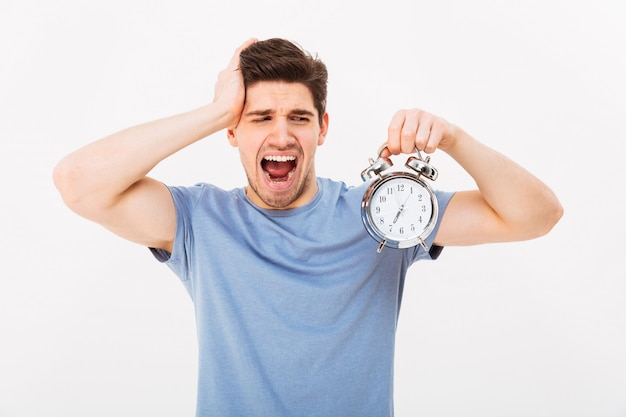 Sleepy young man 30s with brown hair holding alarm clock and yawning in morning, isolated over white wall