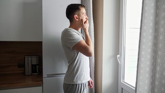 眠そうな青年が台所の窓にあくびをしてやってくる