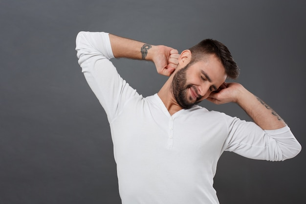 Sleepy young man smiling, stretching after awake over grey wall
