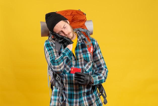 クレジット カードを保持しているバックパッカーと眠そうな若い男