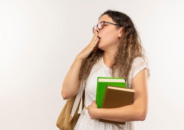 眼鏡とバックバッグを身に着けて本を保持し、白い壁に隔離された目を閉じてあくびをしている眠そうな若いかわいい女子高生