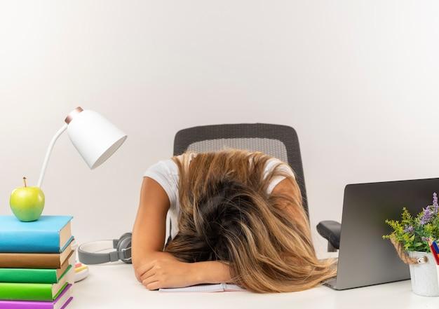 Ragazza giovane e graziosa studentessa sonnolenta che dorme allo scrittorio con gli strumenti della scuola isolati sulla parete bianca