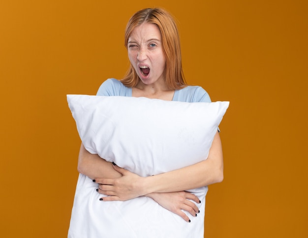 Sleepy young redhead ginger girl with freckles holding pillow and yawning on orange