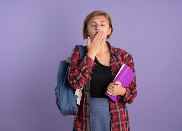 Assonnato giovane studentessa slava che indossa uno zaino mettendo la mano sulla bocca tenendo libro e taccuino